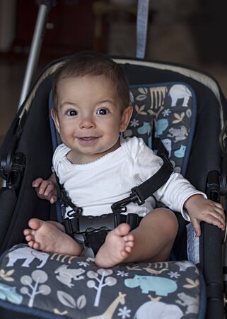 confortable: little baby boy sitting in a stroller in the home, ready for a walk Stock Photo