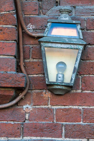 Close-up of the old city lamp on a brick wall of a house in Moscow, Russia photo