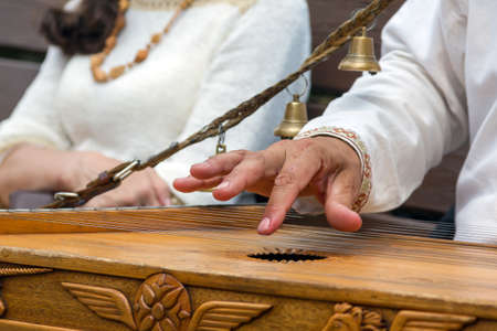 fingering: Russian traditional musical instrument psaltery. Musician playing the harp at the Festival of ethnic cultures in Moscow in the summer