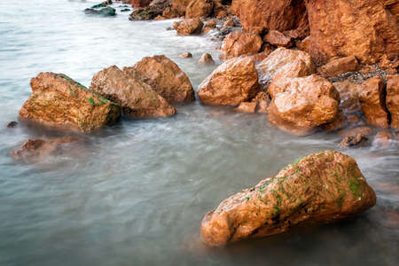 slower: Beautiful stones in sea water at sunset taken at slower shutter speed, the water is like a fog