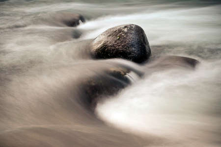 slower: Water, photographed at a slower shutter speed, wraps around the stones that are in the river