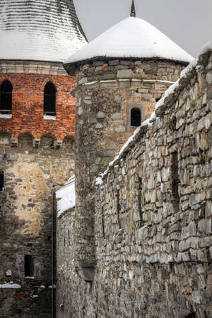 redbrick: The wall of the tower and parts of red-brick castle-fortress in the city of Kamyanets-Podolsky in western Ukraine, winter