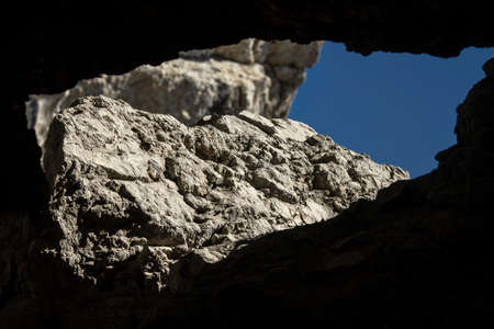 cleft: Cleft in the rock formed a massive window through which one can see the blue sky and stones Stock Photo