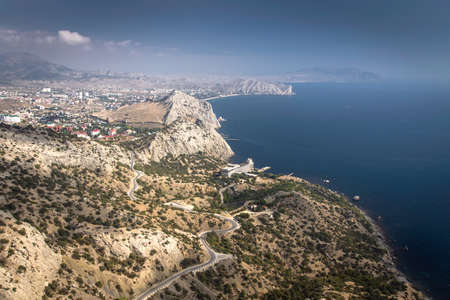 Panorama of Crimean Southern Coast near the town of Sudak birds-eye view. Blue sea, rocky shore and sky photo