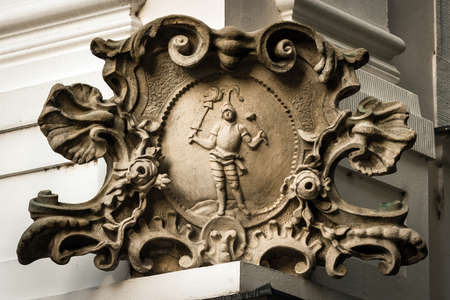 cartouche: Old baroque stone element, cartouche, against the backdrop of the historic house in the capital of Slovakia, Bratislava. Knight with floral elements