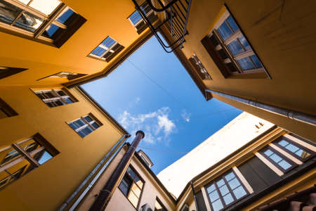 view of an atrium in a building: Bright orange home form at the top of the atrium which shows blue sky. Photographed at the wide angle from below