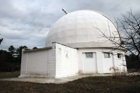 astrophysical: The building with the dome of small telescope on the territory of the historic Crimean Observatory under cloudy dark sky in late autumn Editorial