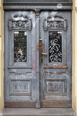 Old wooden door in Prague, painted with gray paint. On the door there is a window with bars, all smeared with graffiti