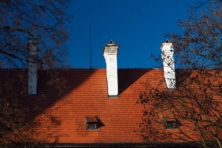 Three chimneys on red tiled roof on one of the historic buildings in the center of Prague on the background of bright blue sky