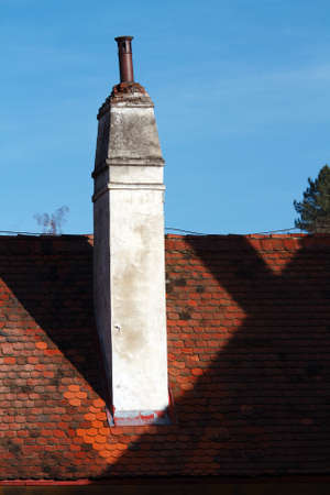close up chimney: Chimney on red tiled roof on one of the historic buildings in the center of Prague on the background of bright blue sky Stock Photo