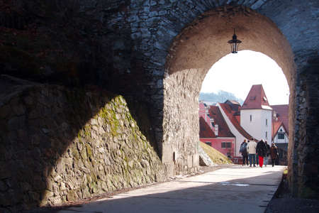 Large group of people passes through the arch, which is overgrown with moss. Against the background of the arch is a famous city of Cesky Krumlov 新聞圖片
