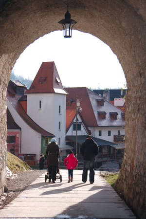 Family passes through the arch, which is overgrown with moss. Against the background of the arch is a famous city of Cesky Krumlov