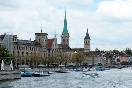 Switzerland, Zurich - May 10, 2019: View of the historic center of Zurich from the canal side on a summer cloudy day