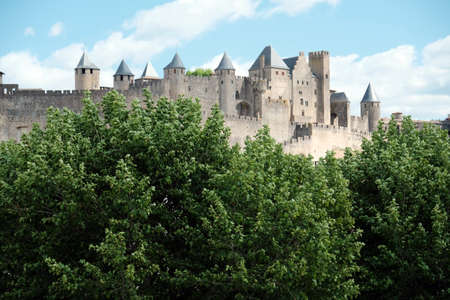 Summer view of the walls of the medieval castle of Carcassonne, immersed in the greenery of the trees. Blue sky, bright colors and ancient walls with towers