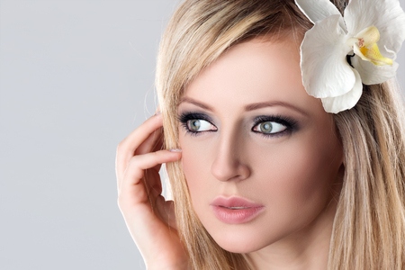 Closeup Beauty Female Face Spa. Beautiful Young Woman Model with White Flower Orchid in Her Blonde Hair touching Cheek.