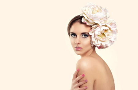 Beautiful Girl With Big Flowers in Head. Beauty Model Woman Face and Body. Perfect Skin. Professional Nude Make-up. Fashion Art. Stock Photo