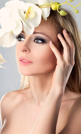 Beauty face of the young beautiful nude woman with orchid flower in her blond hair youching face with clear groomed skin. Stock Photo