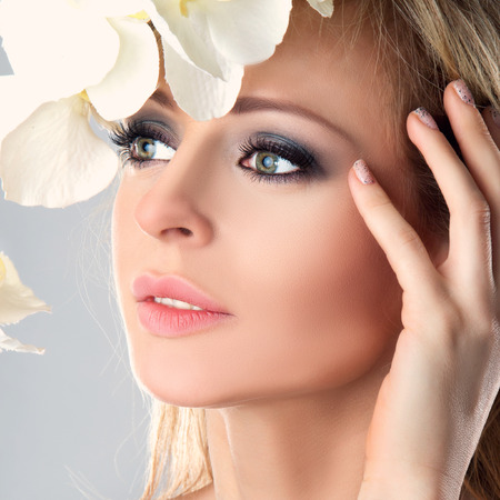 Beautiful Girl With White Orchid Flowers. Beauty Model Woman Face. Perfect Skin. Professional Make-up. Makeup. Fashion Art Stock Photo