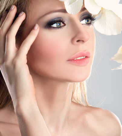 Beautiful Spa Girl With Orchid Flowers. Beauty Woman Touching her Face. Perfect Soft Skin. Skincare concept. Professional Make-up. Makeup photo
