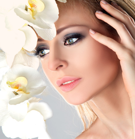 Beauty Female Face with White Orchid flower. Bright Eyes Make up, Long Lashes.