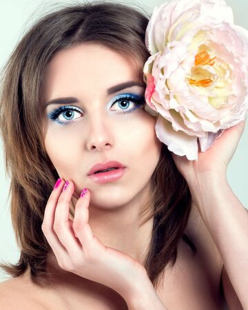 beauty concept - clean face of beautiful young woman with big blue eyes, touching her face, flower in hair Foto de archivo