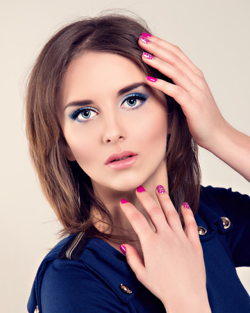 Portrait of the beautiful woman with attractive face and perfect skin posing at studio. Bright manicure.