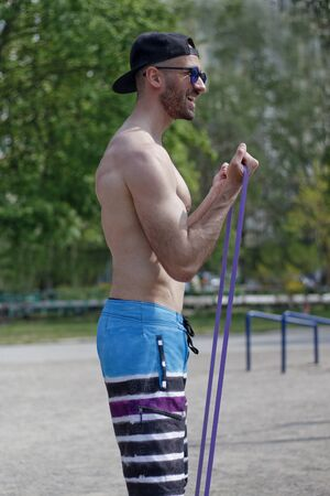 strong young man making hard exercises with rubber in sport park zone