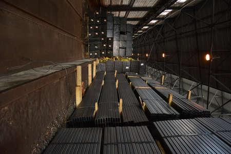 Steel tube. Rectangular steel pipe. Metal pipe. Steel rolled bar. Stuck of steel pipes. Steel pipe bundle in industrial warehouse. Stock Photo