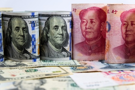 Face to face of Dollar and Yuan banknotes which its are the biggest economic country in the world. Now America and China have increase tax for import goods. It is tariff or barrier trade.
