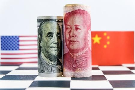 Billete de dólar estadounidense y Yuan con banderas de Estados Unidos y China. Es un símbolo de la crisis de la guerra comercial arancelaria entre el país económico más grande del mundo. Foto de archivo