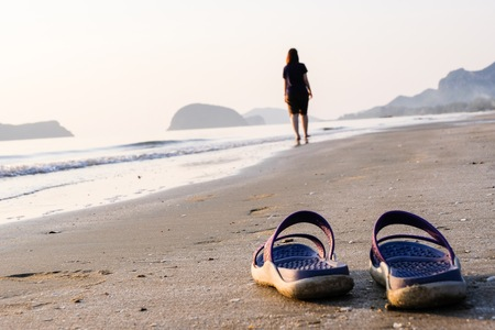 Work Life Balance Concept, woman take a shoes on the beach for relaxation on holiday.