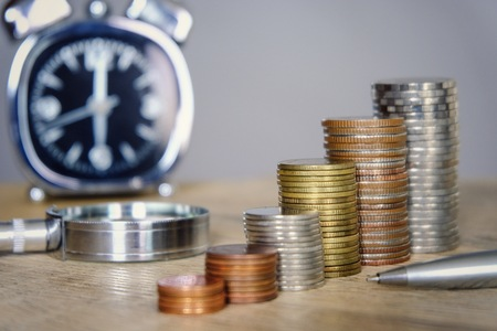 Money coins stacking with clock and magnifier glass for saving and investment concept. Employee and investor have limit time for saving and take more profit.