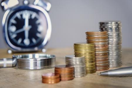 Pièces d'argent empilées avec horloge et verre loupe pour concept d'économie et d'investissement. Les employés et les investisseurs ont un temps limité pour épargner et faire plus de profit. Banque d'images