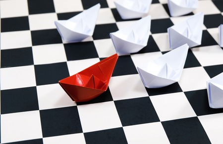 Beautiful blue paper ship moves forward among white ships on the chessboard for leadership concept.