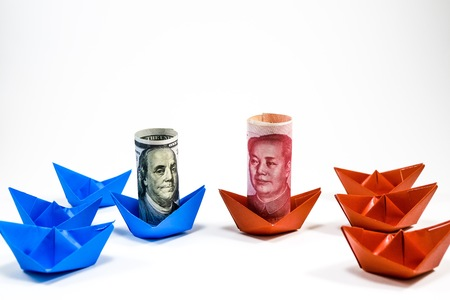 US dollar banknote on blue ship paper and Yuan China banknote on red ship paper on white background Reklamní fotografie