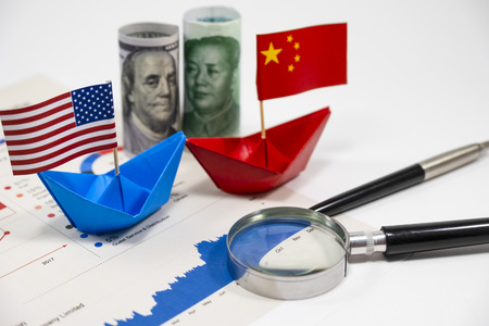 US dollar of United of America and Yuan China banknotes with flag on ship with import export financial report for analysis economy after both countries announce tax tariff trade war. Stock Photo