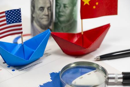 US dollar of United of America and Yuan China banknotes with flag on ship with import export financial report for analysis economy after both countries announce tax tariff trade war.