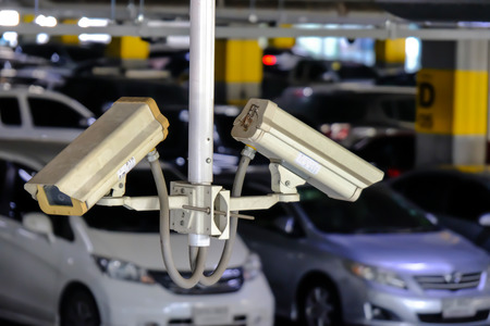 2 CCTV or Close Circuit Television are monitor and record cars in parking lot of shopping mall to prevent robbery and security.