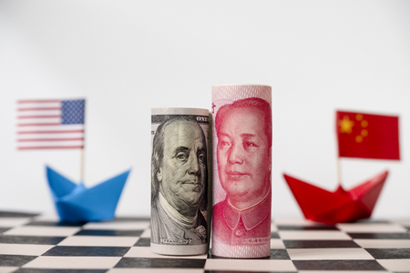 America dollar and Yuan banknote on chessboard with USA and China flags. Its is symbol for tariff trade war crisis between biggest economic country in the world.