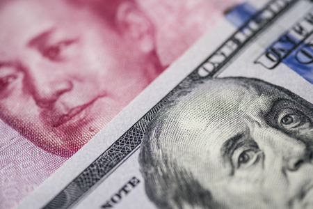 Close up of of China Yuan banknote and US dollar for trade war and economic tax barrier concept. Reklamní fotografie - 115812322