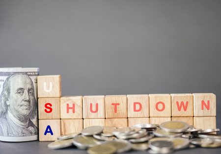 USA shutdown wording on wooden cubes and US dollar banknote and coins on black background. United States of America Government shutdown concept.Image