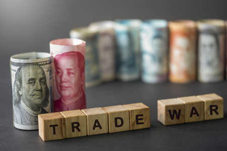 China and USA trade war wording on wooden cubes with US dollar and Yuan banknote on black background.Trade war is economic tariffs tax barrier between China and United States of America.