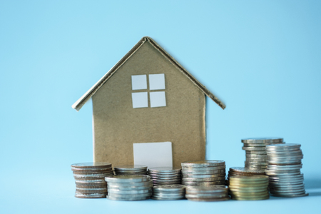 House model around with stacking coins money on blue background. Saving and investment to real estate concept. -image.