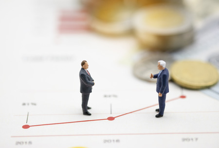 Miniature business men discuss on  line chart of business growth .Copy space and business concept. -Image.