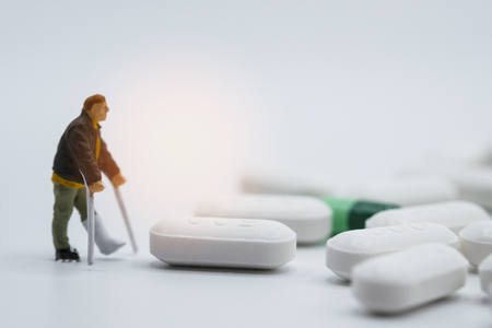 Miniature of old man broken legs around with Pharmaceutical medicine pills, capsules and tablets on white background. Hospital concept - Image Stock Photo