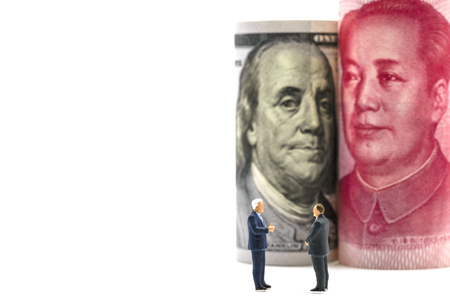 Miniature business men with US dollar and China Yuan banknote on cooperate meeting for trade war.Copy space and business concept. -Image.
