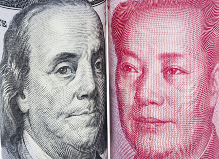 Closeup face to face of Benjamin Franklin and Mao tse tung from US dollar and China Yuan banknotes. Its are 2 biggest economic countries in the world which have tariff trade war.