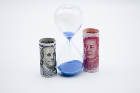 US dollar and Yuan banknote on with sand clock for trade war between United States and China which both countries battle by increase tax barrier and time out of meeting. Government and business.