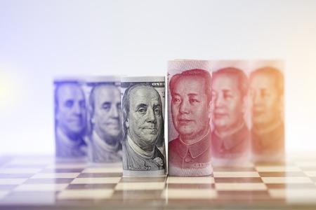 Banknot dolara amerykańskiego i juana na szachownicy oznacza wojnę handlową między Stanami Zjednoczonymi a Chinami, którą oba kraje walczą o zwiększenie bariery podatkowej importu i eksportu produktu. Rząd i biznes.