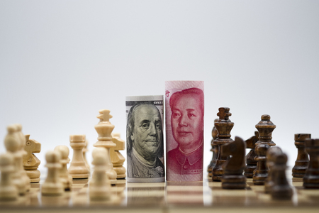 US dollar and Yuan banknote with chess for tariff trade war between United States and China which both countries battle by increase tax barrier of import and export product. Government and business. Stock fotó